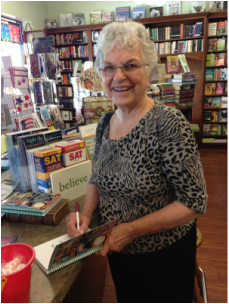 Mary Martin Weyand at Mrs. Figs Book store signing a copy of her children's book Of Giants and Grizzlies.